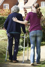 stock photo of zimmer frame  - Daughter Helping Senior Mother To Use Walking Frame - JPG