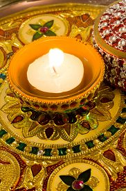 picture of diya  - Traditional diwali diya lamp lit and placed on a beautifully decorated and carved golden plate - JPG