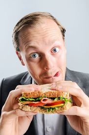 image of sticking out tongue  - Funny humourous man eating a sandwich with exagerrated wide eye comical expression and sticking his tongue out - JPG