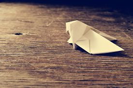 stock photo of yesteryear  - an origami bird on a rustic wooden surface - JPG