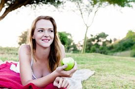 picture of eat grass  - Pretty woman eating and holding half eaten green apple outdoors - JPG