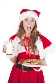 image of santa claus hat  - A young mrs Santa is holding a glass of milk and a plate of cookies - JPG