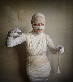 stock photo of fletching  - woman wrapped in bandages as egyptian mummy halloween costume fletching teeth - JPG