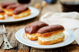 image of eclairs  - eclairs with cheese cream and chocolate glaze on a dark wood background - JPG