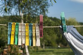 stock photo of clotheslines  - Colored plastic clothesline laundry clips hanging on rope - JPG