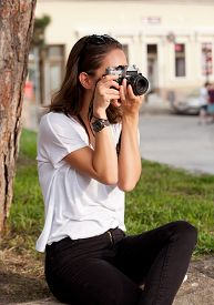 foto of analogy  - Gorgeous young brunette woman using analog camera - JPG