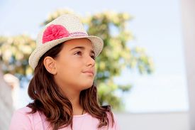 stock photo of ten years old  - Pensive child girl ten year old with a hat on the street - JPG