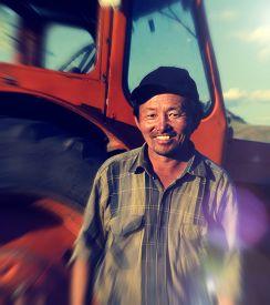 pic of mongolian  - Smiling Mongolian Farmer Standing Next Tractor Concept - JPG