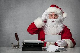 stock photo of letters to santa claus  - Santa Claus typing a letter on an old typewriter - JPG