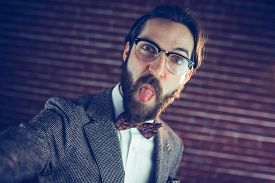 stock photo of sticking out tongue  - Portrait of stylish man sticking out his tongue against brick wall - JPG