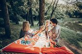 Happy Hipster Family Playing With Cute Little Son On Hammock In Summer Sunny Park. Stylish Mom And D poster