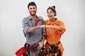 Successful Ecstatic Young Caucasian Man And Female Wearing Overalls And Carrying Working Instruments poster