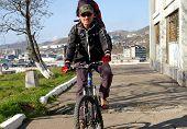 foto of sakhalin  - Man on bicycle travels on city - JPG