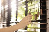 Woman Opening Horizontal Window Blinds At Home, Closeup poster