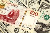 A Close Up Image Of A One Hundred Mexican Peso Bank Note With American One Dollar Bills In Macro poster