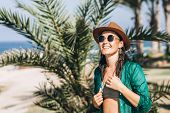 Cute Pan Asian Girl In Hat And Sunglasses In Green Pareo Walking On The Seaside. poster
