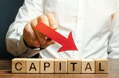Wooden Blocks With The Word Capital And Arrow Down In The Hands Of A Businessman. The Concept Of The poster