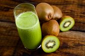 foto of centrifuge  - green kiwi juice and some kiwi on wooden table - JPG
