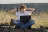 picture of underage  - Resting teen with mobile computer hold hands behind his head in nature at sunset - JPG
