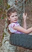 stock photo of tire swing  - This 9 year old Caucasian girl is swining in a tire swing - JPG