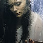 stock photo of boredom  - Art portrait of a beautiful young sadly girl standing at the window watching the rain - JPG
