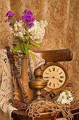 Still Life With Phlox Bouquet In A Vintage Vase On The Old Chair With Antique Clock And Oil Lamp