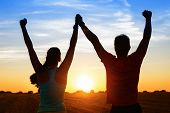 pic of couples  - Successful couple of young athletes raising arms to golden summer sunset sky after training - JPG
