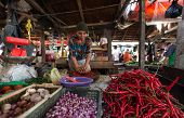 PADANG - AUGUST 25: A vendor grinds up fresh chili, pepper and spices for sale at her stall at an ou