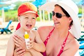 pic of sun tan lotion  - Mom and son on the beach to protect the skin from sun lotion - JPG