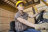 Female industrial worker driving forklift truck with stacked wooden planks in background