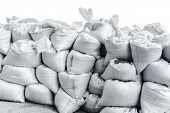 picture of sandbag  - White sandbag bags are full with sand in wall formation and ready for defense - JPG