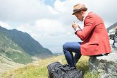 picture of a young fashion man lighting up a cigarette outdoor, in the mountains while sitting on a