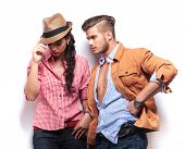 young casual man looking at his girlfriend, she is holding her hat and looks down