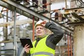 Electrical Engineer with tablet PC in electrical substation