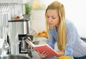 Young Woman Reading Book In Kitchen