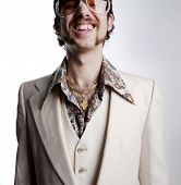 Portrait of a retro man with a gold tooth in a 1970s leisure suit and sunglasses smiling to the came