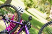 Young woman in helmet trying to fix a chain on mountain bike in the park