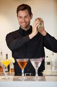 Happy bartender shaking cocktails at the bar
