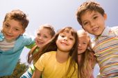 pic of happy kids  - Portrait of happy children smiling while embracing each other with pretty girl in front - JPG