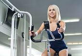 foto of execution  - happy cutie athletic girl execute exercise on exercise bicycle and smile in sport - JPG