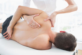 picture of shoulder muscle  - Professional female physiotherapist giving shoulder massage to man in hospital - JPG
