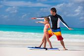 image of boogie board  - Father and daughter at beach practicing surfing position - JPG