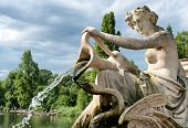 picture of water jet  - Detail of a classical stone fountain with a robed maiden holding an urn spilling a jet of cascading water into the lake below - JPG