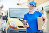 foto of packages  - Smiling female postal delivery courier woman outdoors  in front of cargo van delivering package - JPG