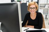 pic of smiling  - Friendly attractive young businesswoman sitting at her desk in the office smiling at the camera past her computer monitor - JPG