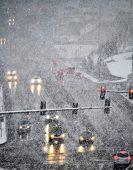 stock photo of icy road  - Snowy winter road with several cars driving on roadway with traffic lights - JPG