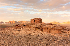 stock photo of empty tomb  - Ancient Nabatean tombs at sunset in the remote desert - JPG
