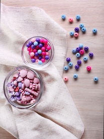 foto of crown green bowls  - Different beads in glass bowls on fabric on table - JPG