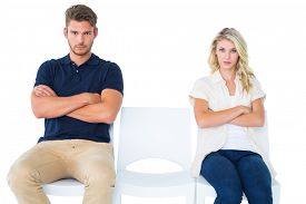stock photo of not talking  - Young couple sitting in chairs not talking during argument on white background - JPG