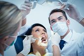 pic of dentist  - Male dentist with assistant examining womans teeth in the dentists chair - JPG